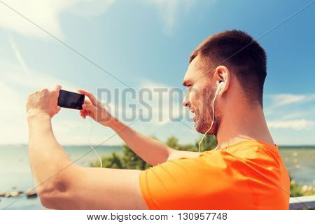 fitness, sport, people, technology and healthy lifestyle concept - smiling young man with smartphone and earphones listening to music at summer seaside