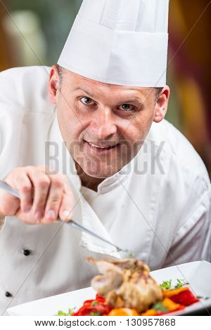 Chef. Chef cooking.Chef decorating dish. Chef preparing a meal. Chef in hotel or restaurant kitchen prepares decorating dish with tweezers. Chef cooking only hands. decorating grilled quail