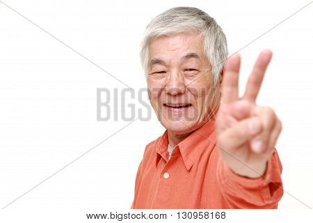 portrait of senior Japanese man showing a victory sign on white background