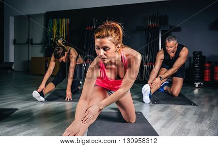 People stretching legs in fitness class before training on sports center