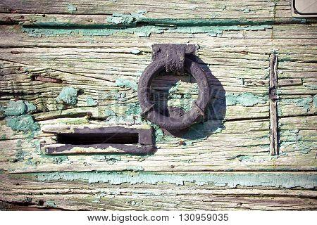 Metal knocker door on a wooden ancient door