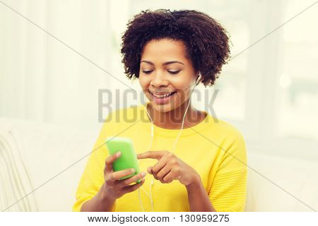 people, technology and leisure concept - happy african american young woman sitting on sofa with smartphone and earphones listening to music at home