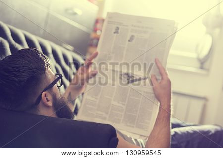 Male model lyingon a couch in a living room reading newspapers