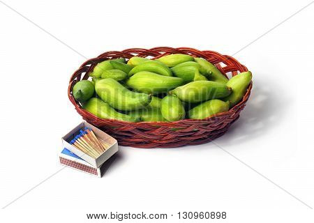 small basket with many small green unripe fruits of caigua appropriate for the marinating on white background with matchbox and matches