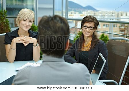 Happy young businesswomen sitting around table outdoor on office terrace and talking, smiling. Over the shoulder view.