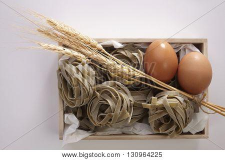 Italian pasta fettuccine nest, egg and wheat ears still life isolated on white background