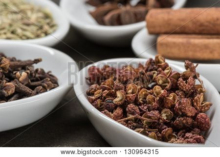 Szechuan Peppercorns in White Spoon with chinese five spices in background