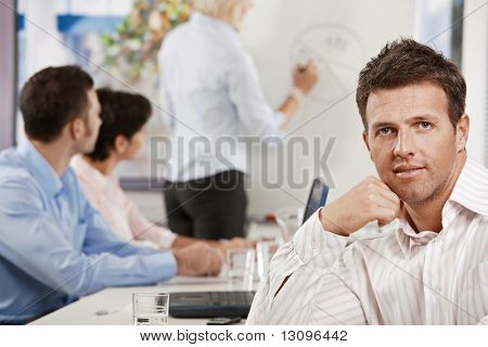 Satisfied mid-adult businessman in business meeting at office, looking at camera smiling.