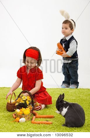Easter image: smiling little girl with Easter bunny on green carpet.