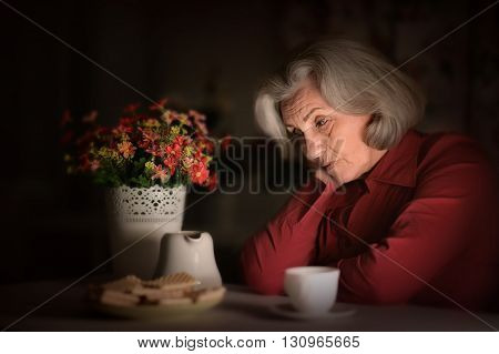 Portrait of an old woman sitting in the evening at home with tea and sweets