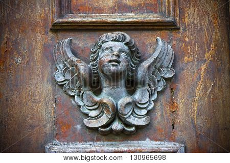 Sculpture of an angel on a wooden door in Italy - toned image