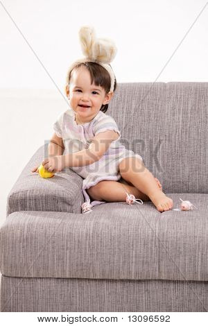 Baby girl in easter bunny costume, sitting on grey couch playing with toy chicken and easter eggs, laughing. Isolated on white background.