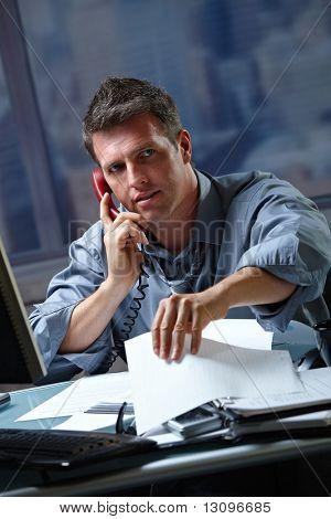 Mid-Adult empresario habla sobre fijo teléfono trabajando a destajo en la oficina de control de documentos.