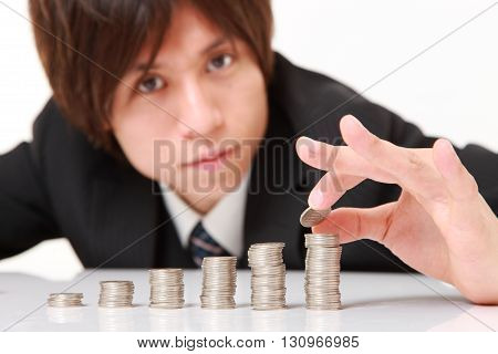 Businessman Put Coins To Stack Of Coins