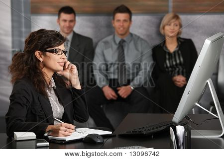 Junge geschäftsfrau sitzen am Schreibtisch im Büro Recepcion, talking on Mobile Phone, Lächeln, Leute wa