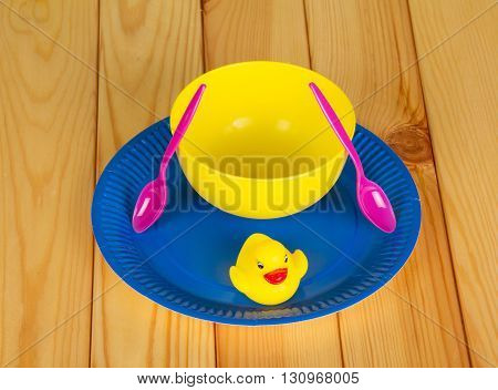 Colored plastic ware and rubber duck on a background of light wood.