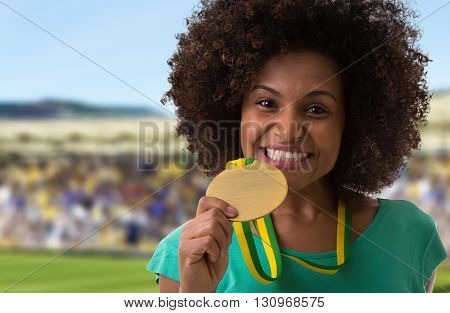 Afro woman holding a gold medal in the stadium