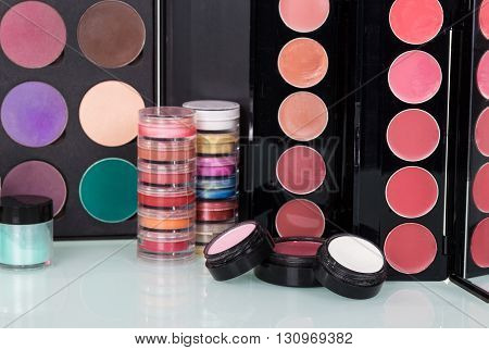 Professional cosmetics: eyeshadow, lip gloss, blush and powder make-up background.