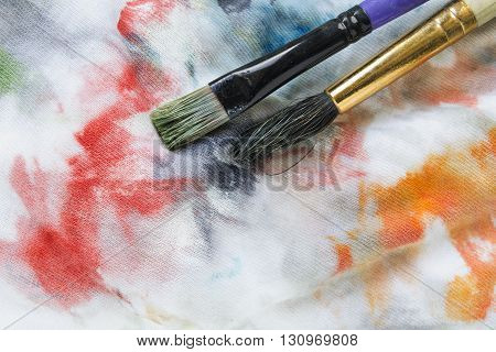 Two paint brushes on stained colorful canvas as a background