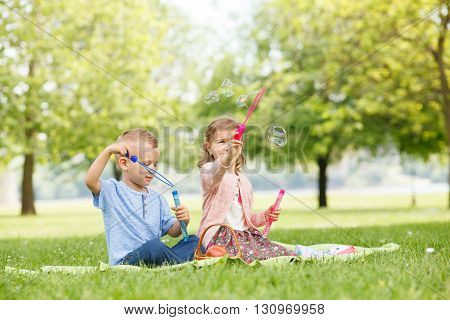 Little brother and sister having fun with soap bubbles in the park