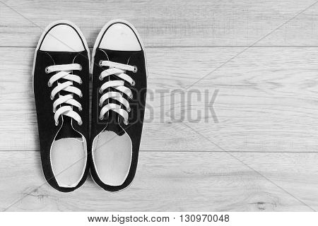 Pair of black gumshoes on wooden floor