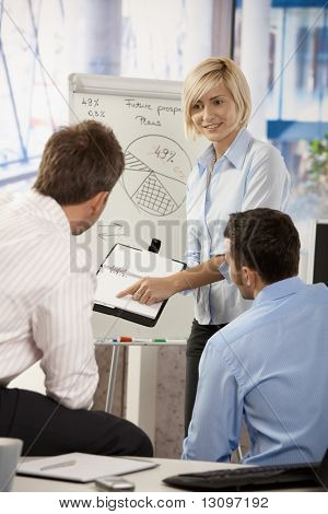 Young businesspeople working together in office, using notebook and whiteboard.
