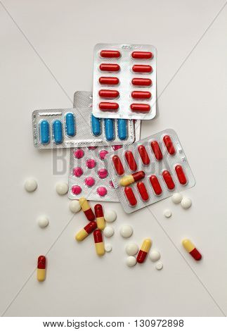 packs of colorful pills in blisters and a lot of scattered pills and capsules around