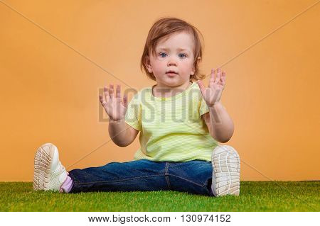 One cute and funny baby girl on grass and orange background