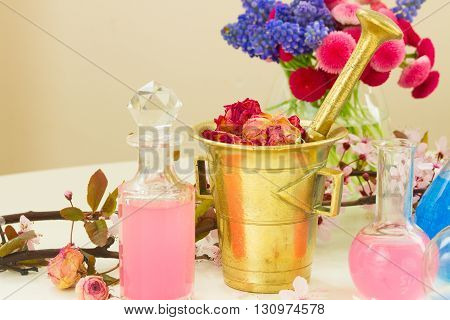 Dry flowers in brass mortar and vials of tincture or oil, aromatherapy and herbal medicine concept