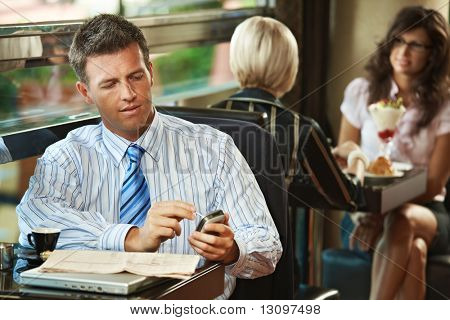Businessman sitting at table in cafe using mobile phone. Young women having sweets in the background.