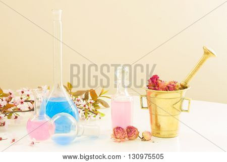 Dry flowers, mortar, vials and bottles of tincture or oil, aromatherapy concept