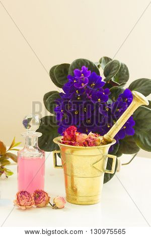 Dry and fresh flowers, mortar and vial of potion, herbal medicine