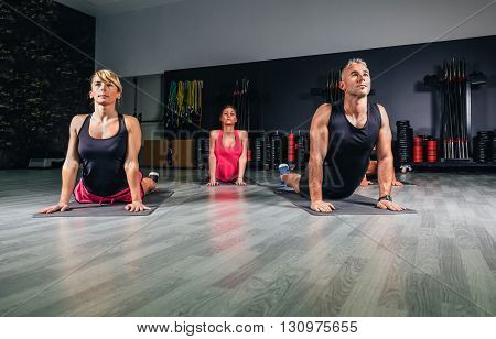 People stretching their backs in fitness class before training on sports center