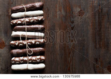 Chocolate cake sticks on dark wooden background. Black, white and decorated chocolate cake sticks. Flat lay. Sidepiece. Free space, void. Vertical line