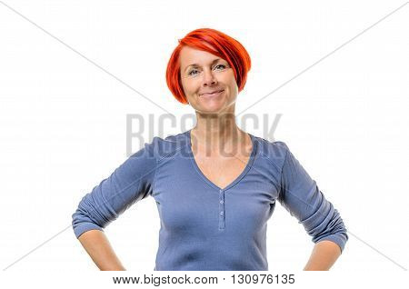 Single smiling cute mature woman in blue shirt and short red hair with hands on hips over white background