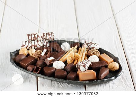 Assorted chocolate candies on black clay plate. White wooden background with free space on top. Different sorts of chocolate candies front view.