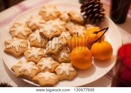 Christmas coockies and mandarines on white plate