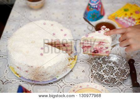Cutting white strawberry cake with a knife