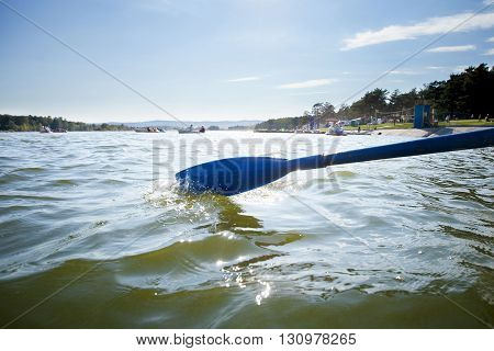 Boat paddle on water of lake, rowing