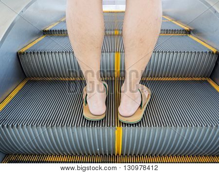 Man legs step on the escalator with shorts