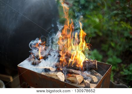 Burning wood in a brazier. Fire, flames from wood ember for grill or bbq