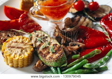 Tasty grilled colorful vegetables on white plate. Red sause. Extreme close-up of vegetarian grilled vegetable food. Light background.