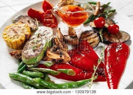 Plate with grilled vegetables set and sauce. Flat lay of vegetarian vegetable bbq. Closeup of grilled vegetables set on white background.
