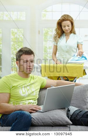Man with broken leg resting on couch, using laptop computer. Woman doing ironing at the background.