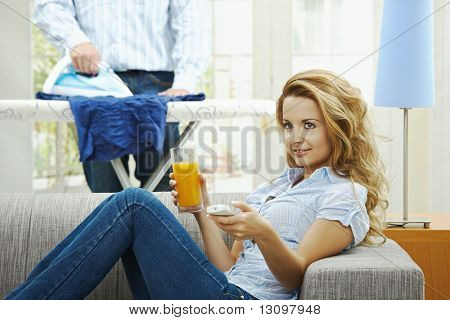 Happy woman sitting at couch watching TV, man ironing in the background. Selective focus on woman.