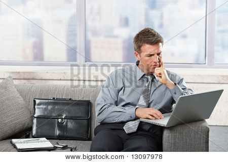Focused businessman working on laptop computer sitting on sofa in scyscraper building.