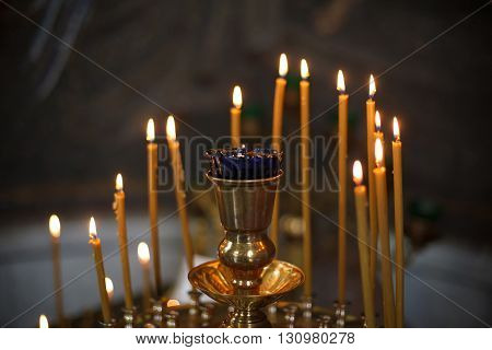 Lighting yellow candles in Orthodox Church, Russia