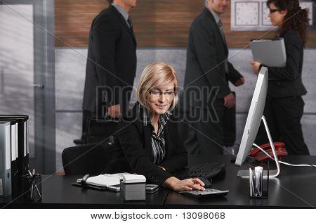 Junge blonde geschäftsfrau sitzen am Schreibtisch, mit Taschenrechner, lächelnd.