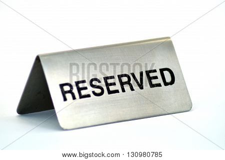 Plate of reservation of table of aluminum restaurant on white bottom.