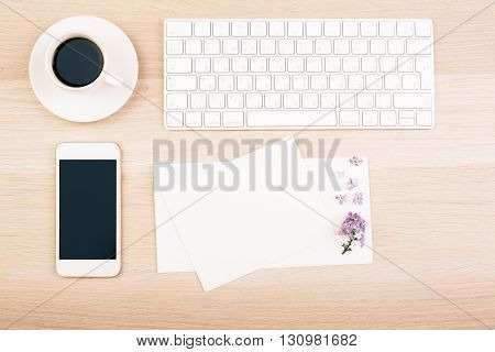Top view of wooden desktop with blank smart phone emty cards coffe cup and keyboard. Mock up